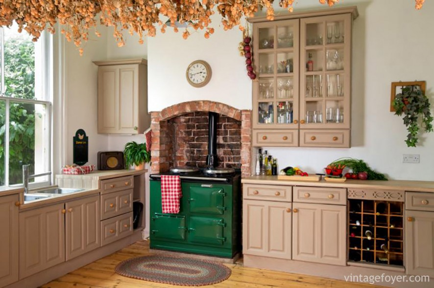 If you're looking for a cozy cottage feel for your kitchen, try including red brick. The pink hues of the cabinets are a beautiful contrast to the brick and bright green vintage stove.