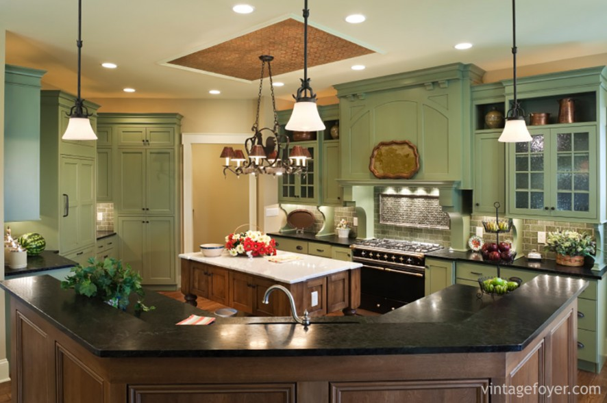 The unique vintage green cabinets of this kitchen are accented by the dark marble countertops of this wrap around island. Including a small center island, this kitchen is vibrant and colorful.