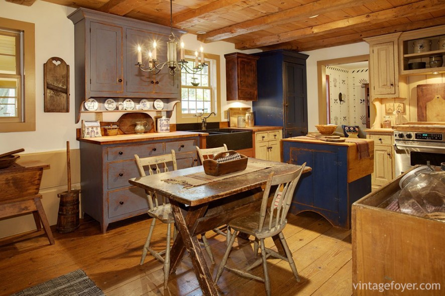 This kitchen is full of interesting colors and textures that delight the eye: a rustic, wooden table; blue cabinet and island; wooden floors and matching wooden ceilings.