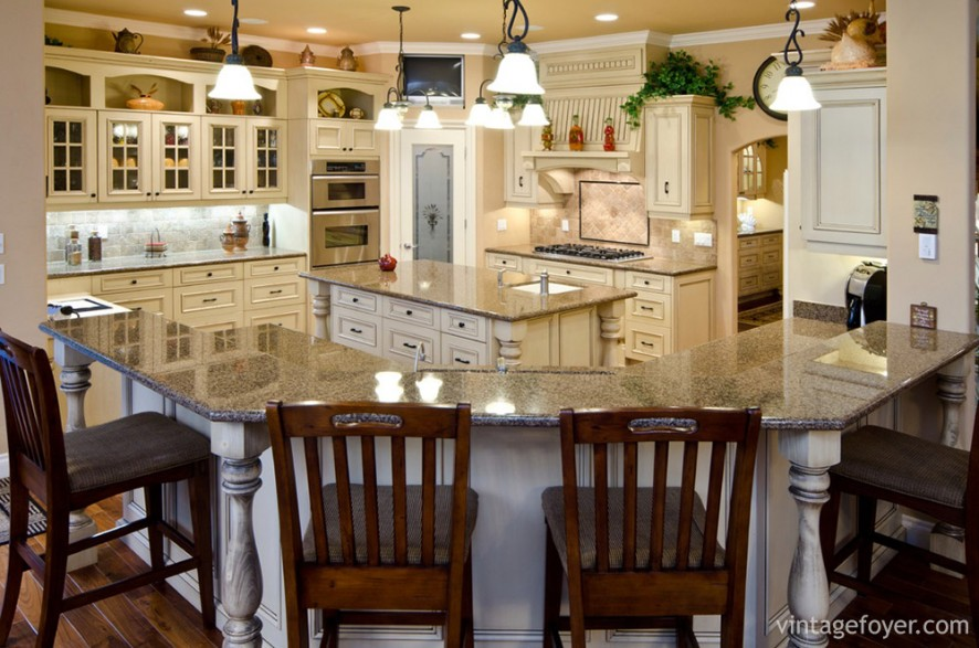 This traditional yet welcoming kitchen is perfect for a large number of guests. With its large wrap-around counter top and island, its cottage-style glass cabinets and red-stained bar chairs, this kitchen is open but warm and colorful.