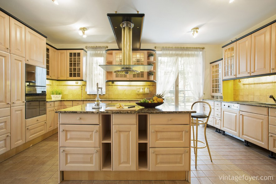 Warm and honey colored, this kitchen is alive with natural light and floor-to-ceiling cabinet space. The dark marble counter tops provide a nice, natural contrast to the cream-colored floors and cabinets.