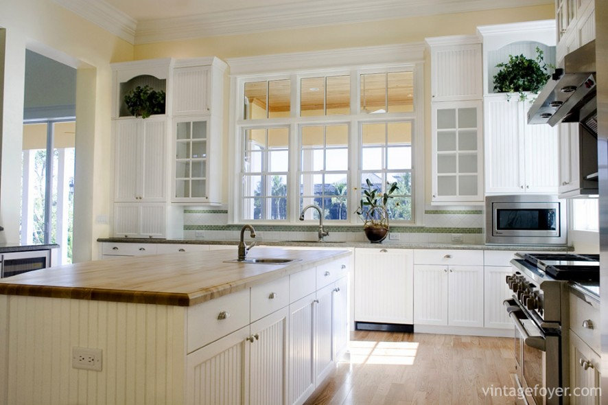 Details make all the difference. This kitchen infuses cottage-style living with modernity by using paneling on the white cabinets and choosing glass doors for the cabinets to enhance the natural light.