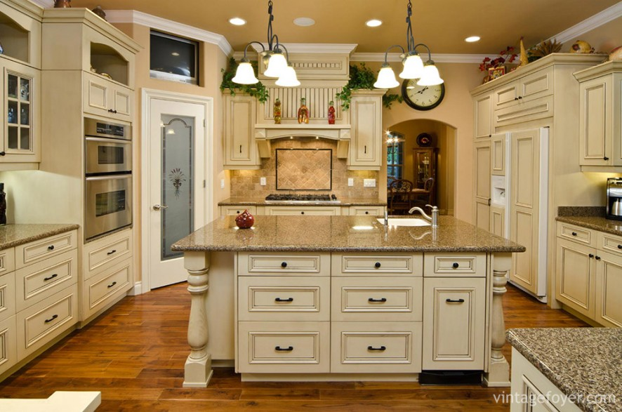 The elegance of this kitchen comes from the variety of colors and textures: cottage-style doors; the metal fixtures on the cabinets; the busy design of the marble countertops; and the hanging three-piece light fixtures.