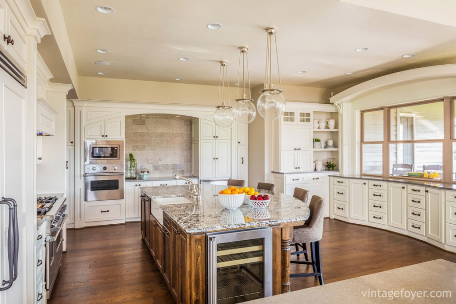 The perfect combination of kitchen and dining room: the large, oval shaped island is perfect for cooking and dining, surrounded by beautiful cream colored cabinets.