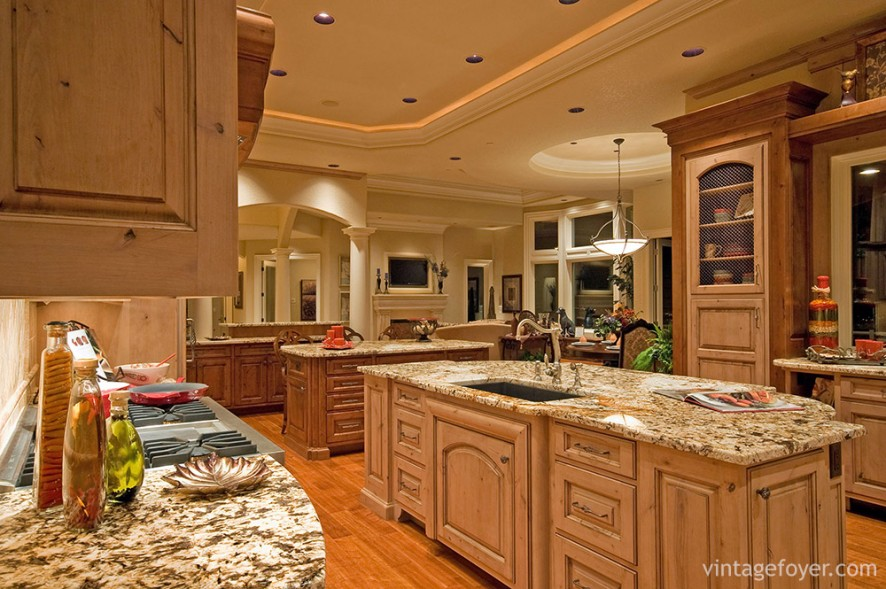 A vibrant mixture of wood and marble bring this kitchen to life. The intricate design of the countertop coupled with the soft lighting creates an atmosphere of luxury and sophistication.