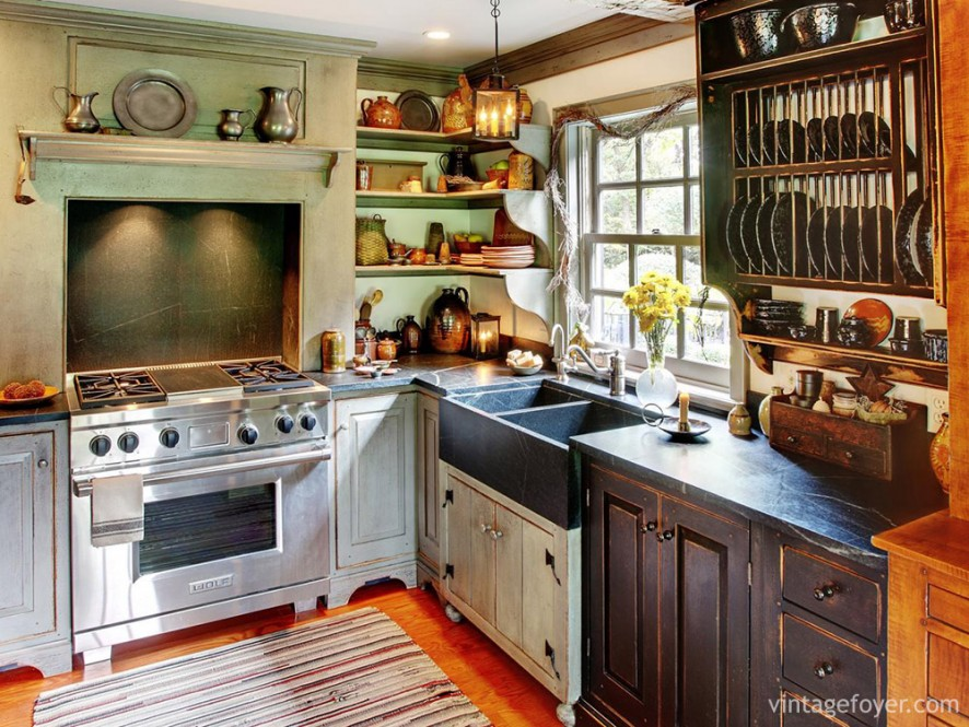 Busy, colorful, and cozy, this kitchen is full of character: exposed racks for plates and cups, differently stained wood cabinets, vintage green walls, and a striped floor mat.
