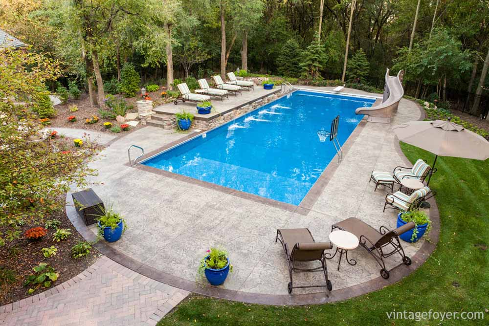 here we have a simple rectangular pool that has a slide attached and plenty of patio space for lounging or entertaining this in ground pool is accented - Rectangle Pool Aerial View