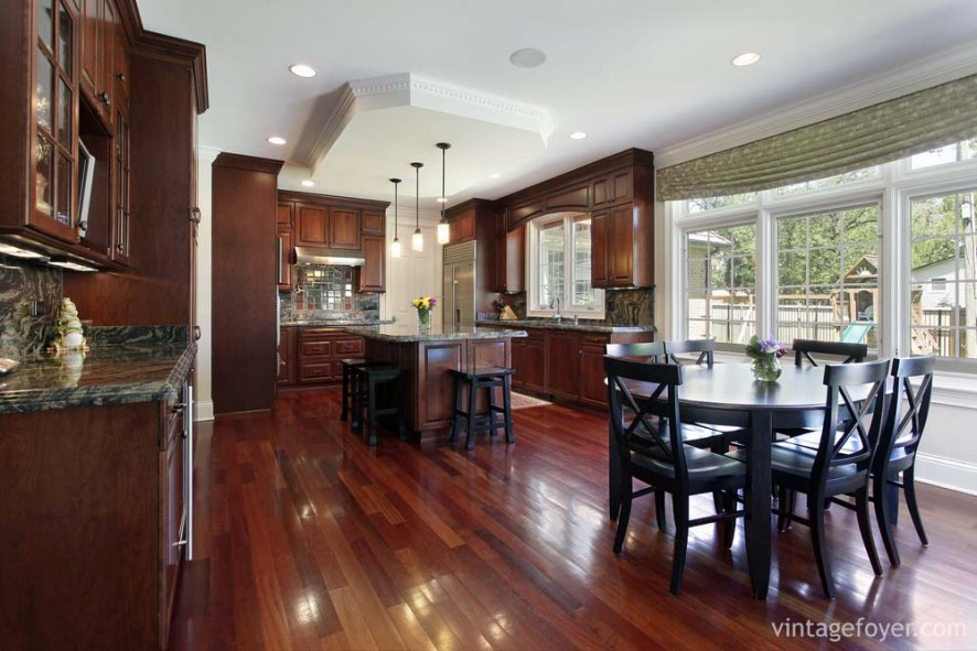 Dark cherry hardwood flooring and custom traditional cabinetry, and black and grey marble countertops throughout.