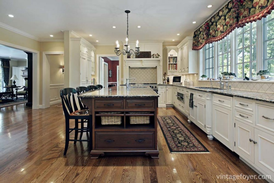 Medium toned hardwood flooring, dark toned island, and white custom cabinetry with matching black speckled marble countertops.