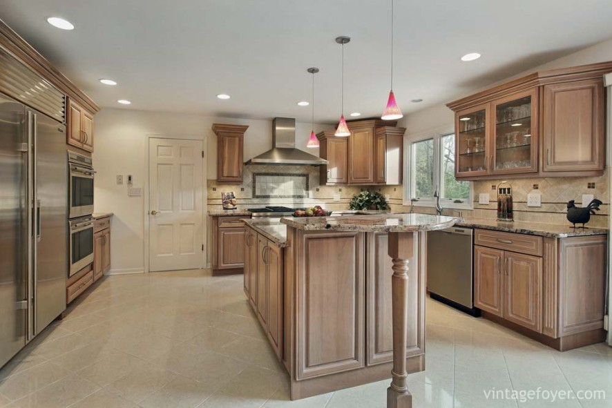 High end stainless steel appliances, light toned traditional style cabinetry, and beautiful tan marble countertops.