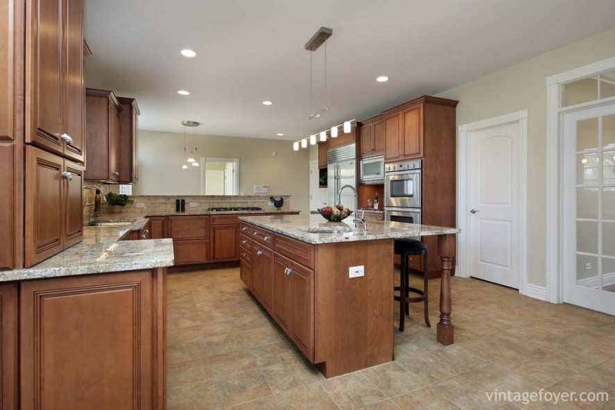 Stainless steel appliances, light tan marble countertops, beautiful multi-toned porcelain tile, and custom cabinetry.