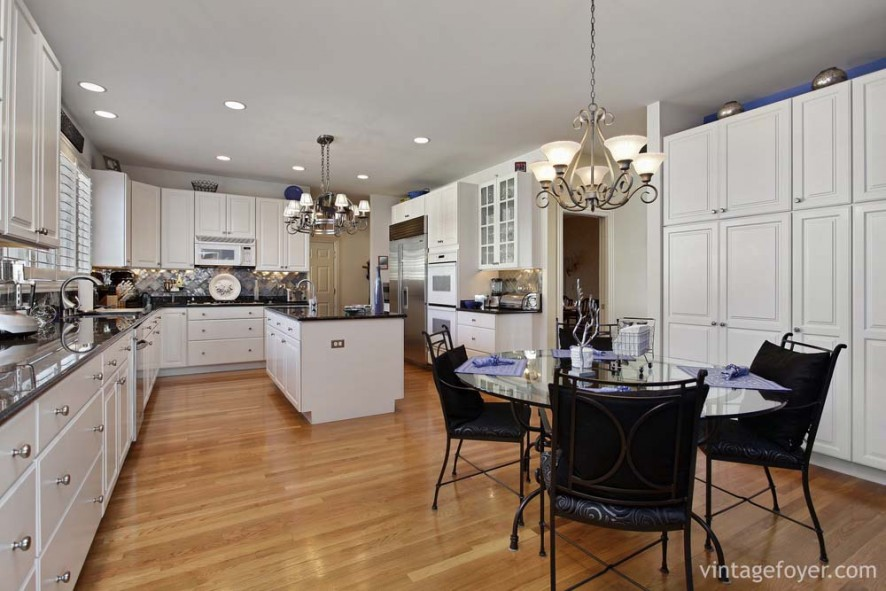 Light toned hardwood flooring, beautiful black marble countertops, and white custom cabinetry.
