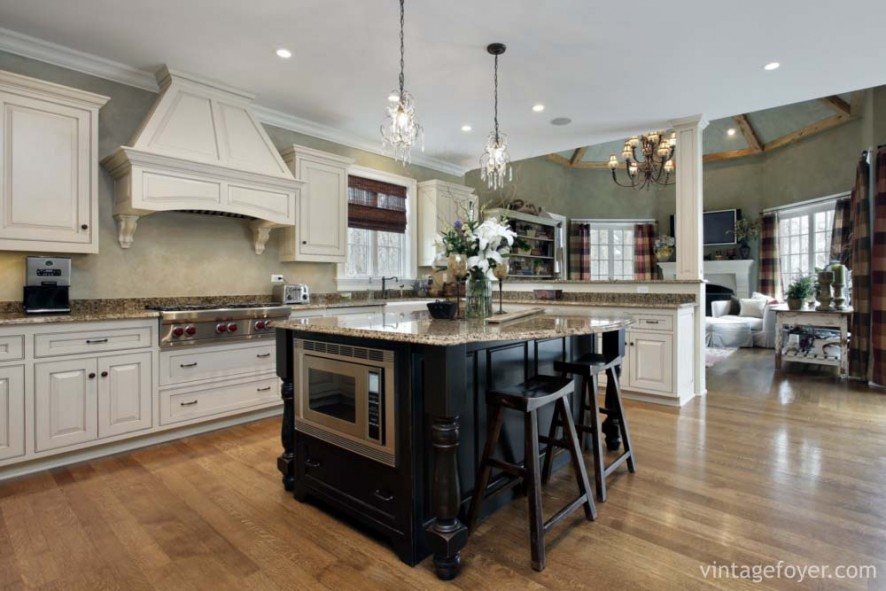 Custom white cabinetry and oven hood, beautiful tan speckled marble countertops, and a contrasting black island.