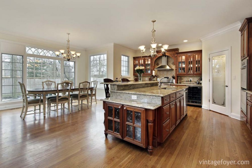 Large open concept, beautiful custom cabinetry with white/grey marble countertops, stainless steel appliances, and light toned hardwood flooring.