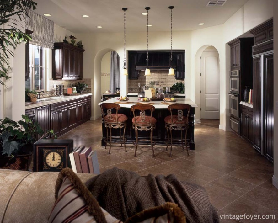 Large open kitchen with dark toned hardwood cabinetry, white quartz countertops, and tan toned porcelain tile flooring.