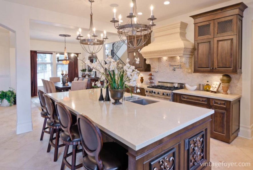 Custom designed island and cabinetry with white quartz countertops, custom oven hood with beautiful architectural details, elegant cream toned porcelain tile flooring.