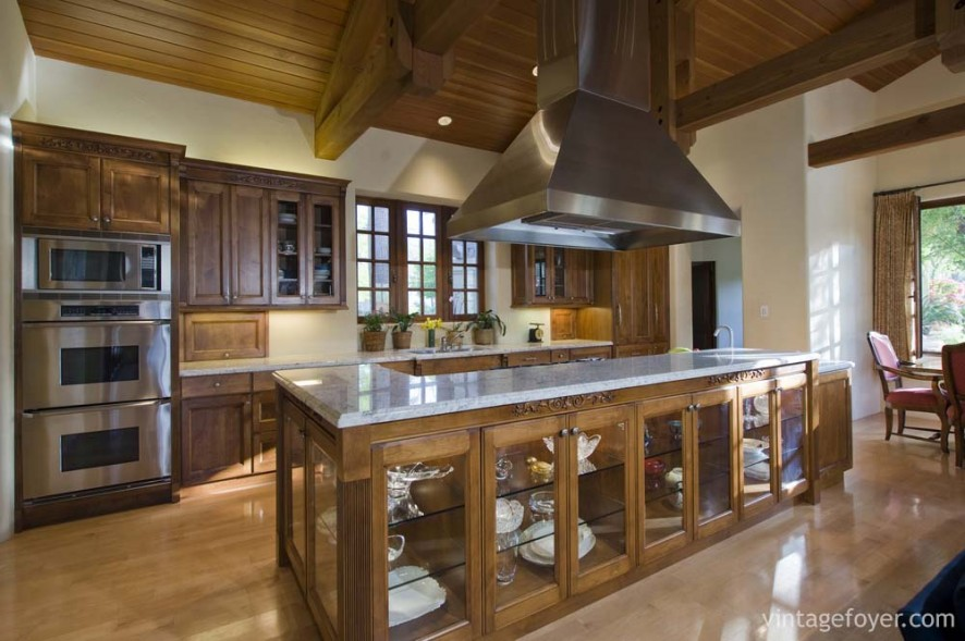 Traditional style dark toned cabinetry with architectural accents, Beautiful clear glass doors on the island, and white swirled marble countertops.