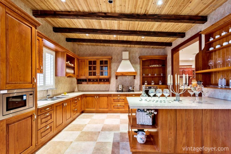 Multi-colored tile flooring, medium toned traditional style cabinetry and island with quartz countertops.