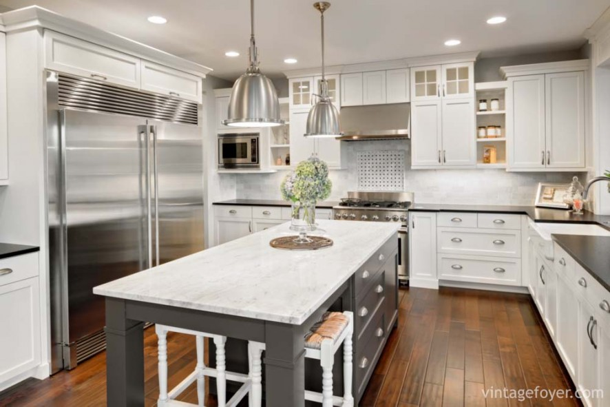 High end stainless steel appliances, white marble countertop on a grey island, custom white shaker cabinetry with a black quartz countertop, and a dark toned hardwood flooring.