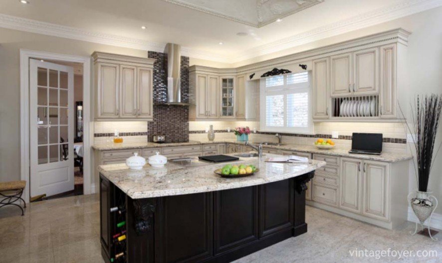 Black island with white speckled marble countertop, custom traditional cabinetry with the same beautiful countertop, custom black backsplash, and high end appliances.