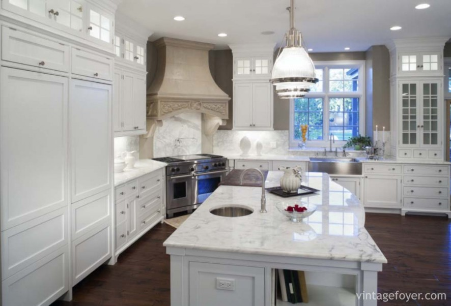 Luxurious white marble residential kitchen with hardwood floors, stainless steel appliances, and white enamel custom cabinets.