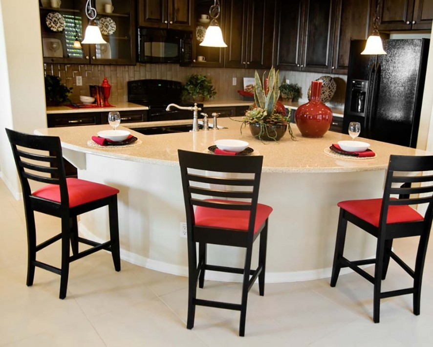 Beautiful large modern kitchen island area in new home with bar stools